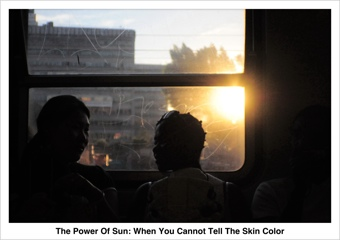 the strong sun makes all a silhouette, therefore you cannot tell the skin color of two mysterious women sitting before a train window