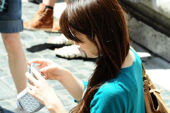 asiatica che guarda un telefonino assorta